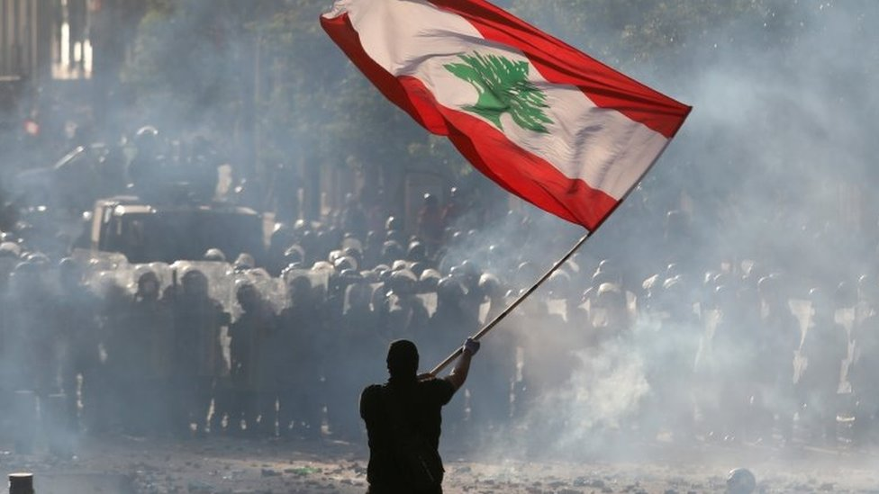 A man holds a Lebanese flag near riot police at a protest on 8 August 2020