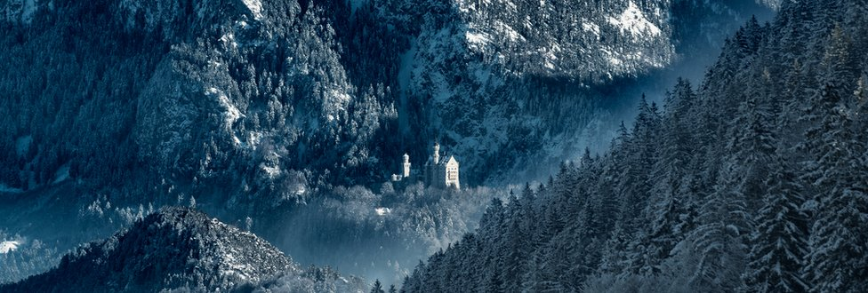 A snowy mountainous landscape with a castle perched on a hill