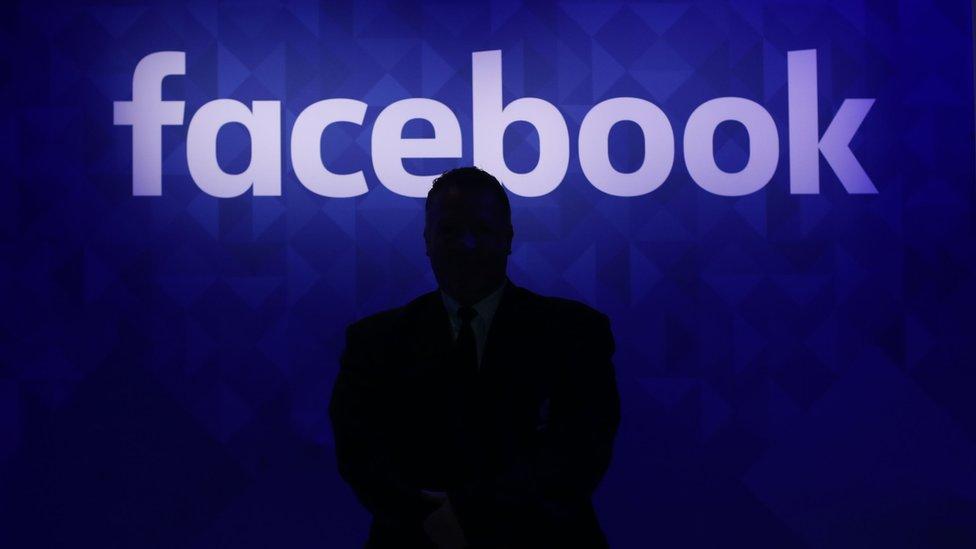 شخص يقف امام علامة فيسبوك التجارية