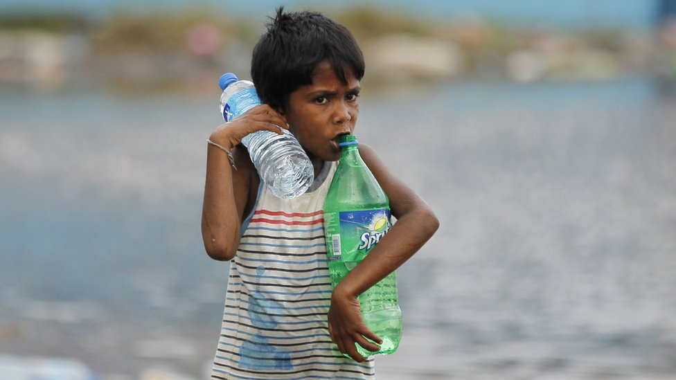 A Sri Lankan boy carries water bottles near a flood affected area near Colombo, Sri Lanka, Sunday, May 22, 2016.