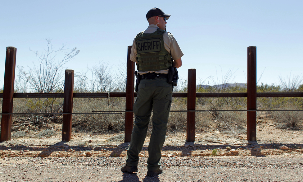 """A Douglas County Sheriff""""s Office deputy stands in front of the US border with Mexico while Republican presidential candidate Sen Ted Cruz visits the border with Mexico in Douglas, Arizona"""