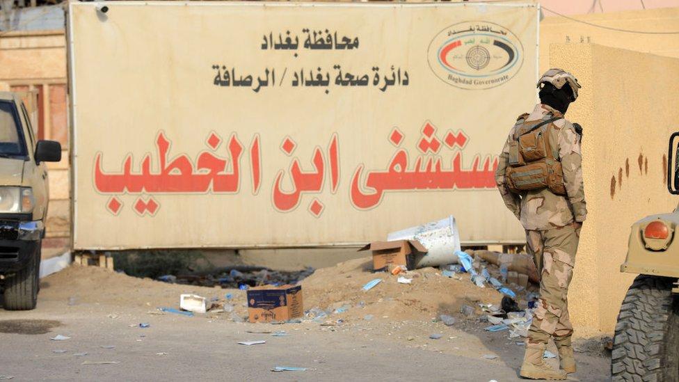 جندي يقف أمام لافتة عليها اسم مستشفى ابن الخطيب