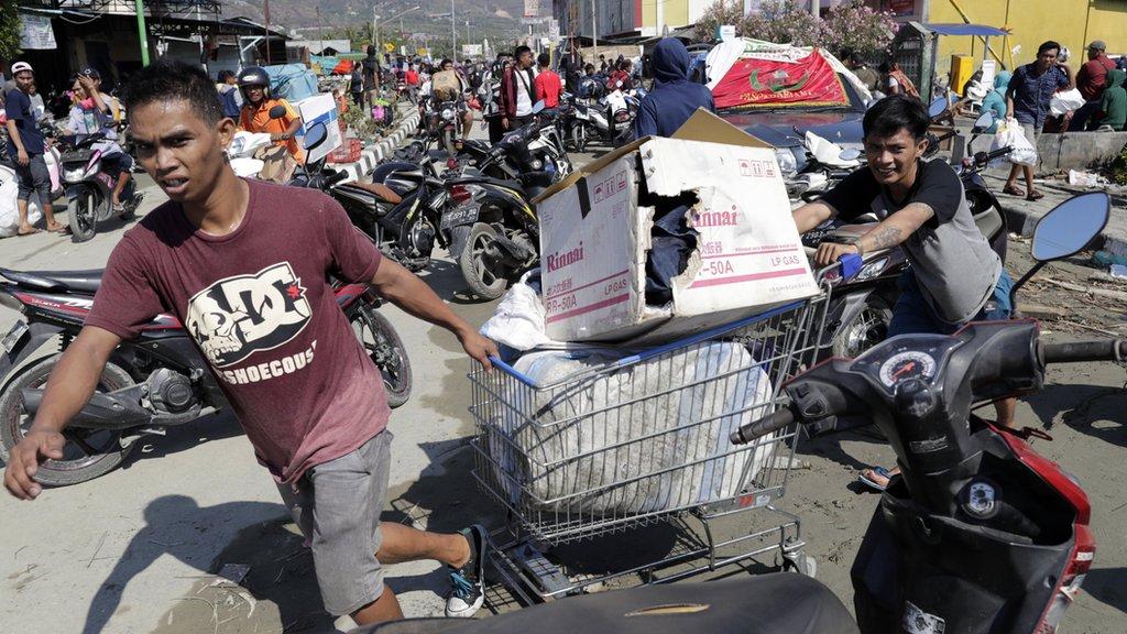Ljudi vuku kolica iz prodavnice sa ukradenom robom. 30. septembar