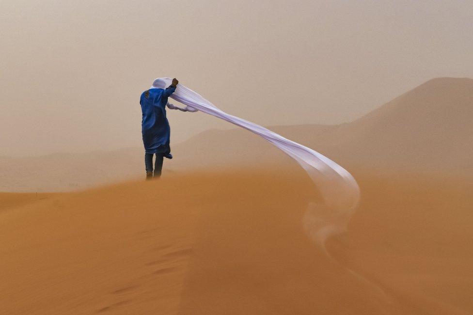 Čoveku vetar odnosi maramu koju je nosio oko glave dok je bio u pustinji Sahari