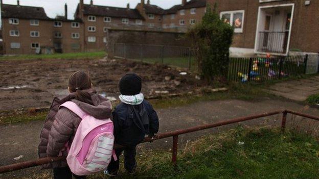 Children in coats sit on railing