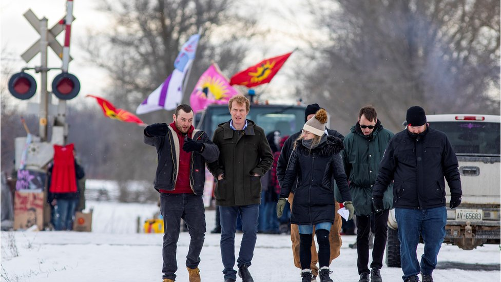 Indigenous Services Minister Marc Miller walks with representatives of the Mohawk Nation