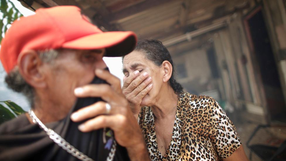 Um homem e uma mulher cobrem os rostos com as mãos em área externa de casa, tentando se proteger de fumaça