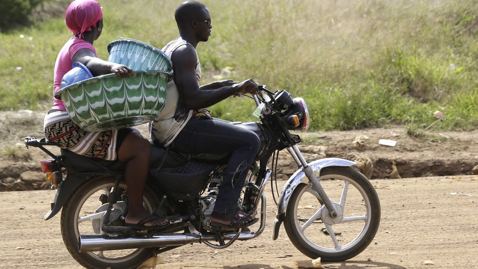 A woman carrying two plastic containers on a motorbike taxi in Monrovia, Liberia - Tuesday 26 November 2019