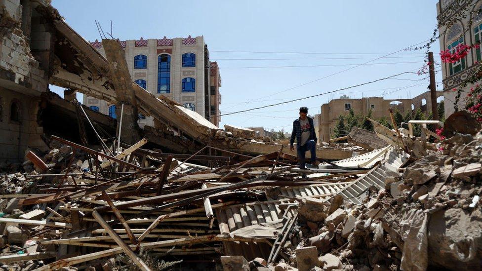 رجل يمني يتفقد منزلا دمر في غارة جوية نفذتها طائرات التحالف بقيادة السعودية في 5 فبراير/شباط 2021 في صنعاء، اليمن