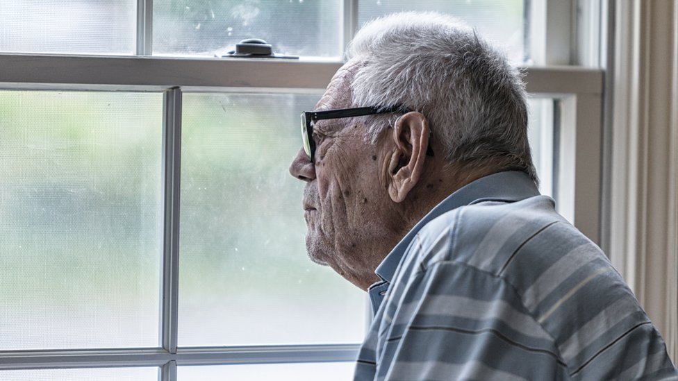 An elderly man look out of the window