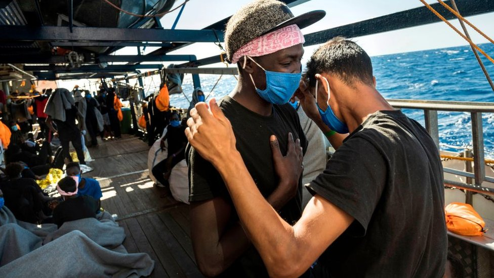 A Libyan migrant (R) and an east African migrant pray a Muslim prayer for reconciliation onboard the Sea-Watch 4 civil sea rescue ship on September 01, 2020, on sea off the coast of Sicily, Italy,