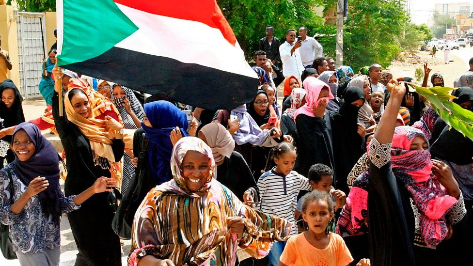 Sudanese demonstraters wave their national flag as they celebrate in Khartoum