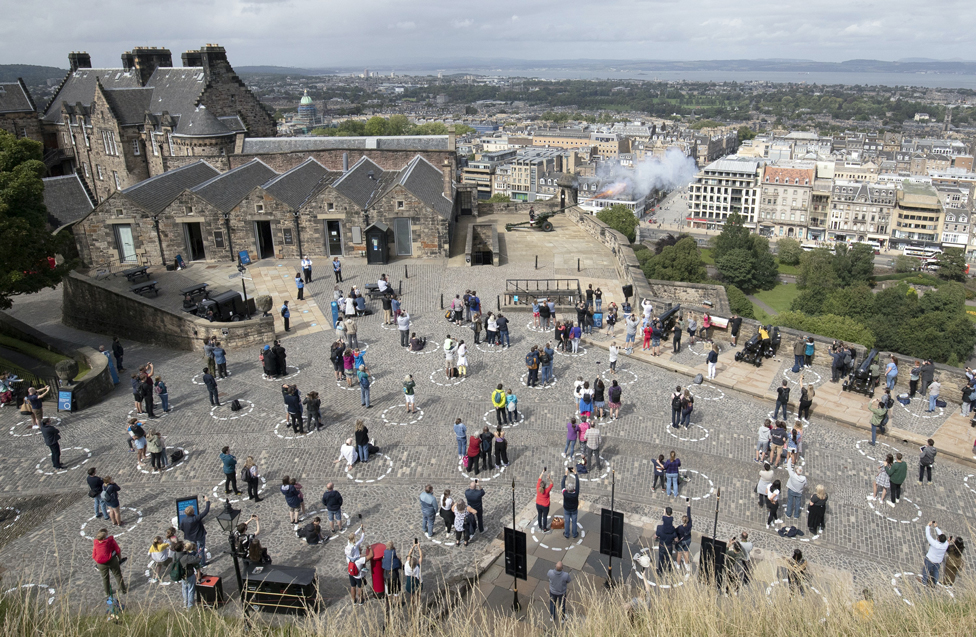 Visitors at Edinburgh Castle standing socially distanced in marked out circles