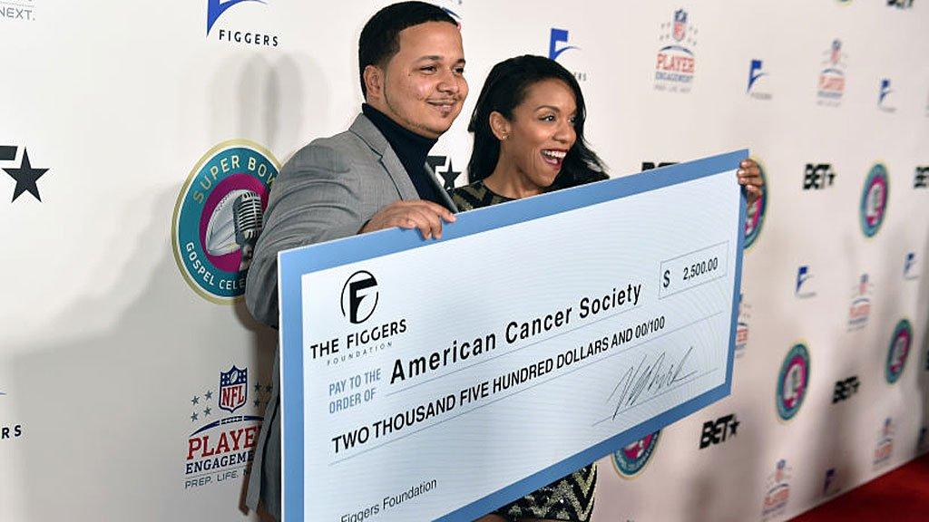 Figgers con un cheque para cáncer