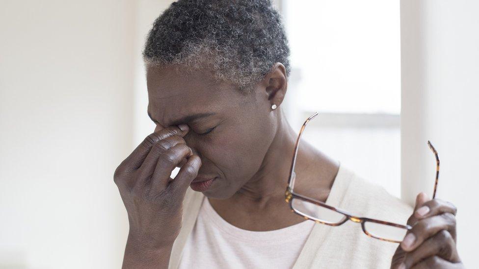 Una mujer se toma los ojos con los lentes en una mano.