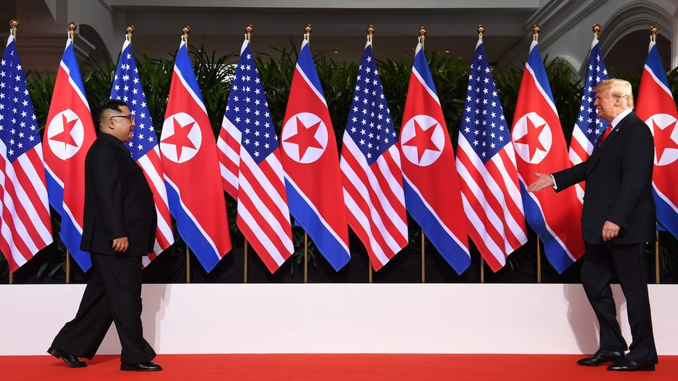 "US President Donald Trump (R) and North Korea""s leader Kim Jong Un (L) walk toward one another at the start of their historic US-North Korea summit, at the Capella Hotel on Sentosa island in Singapore on June 12, 2018."