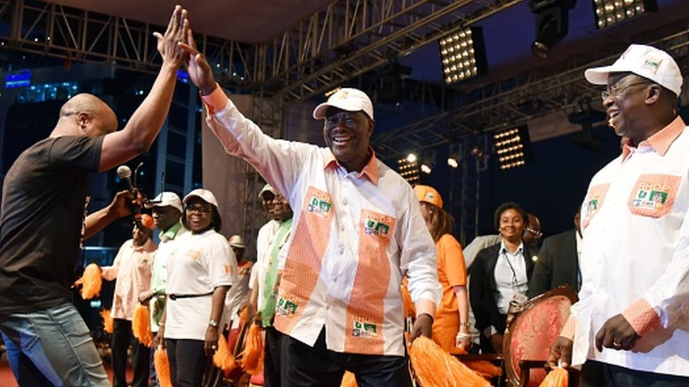 Alassan Ouattara (C) dances with the singer Asafo (L) of the group Magic System at the end of a campaign parade on 23 October 2015 in Abidjan