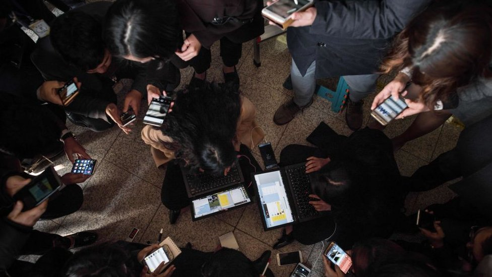 Grupa ljudi kuca na mobilnim telefonima i tabletima