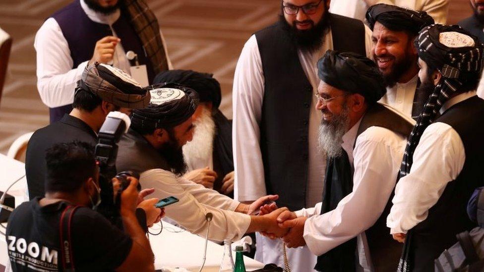 Los delegados talibanes estrechan manos en las negociaciones con el gobierno afgano en Doha, Qatar.