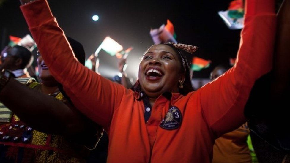 A supporter of presidential election candidate of Burkina Faso Roch Marc Christian Kabore celebrate after preliminary results showed him to be the winner of recent elections, supporters gather outside Kabore's campaign headquarters in Ouagadougou, Burkina Faso, Tuesday, Dec. 1, 2015