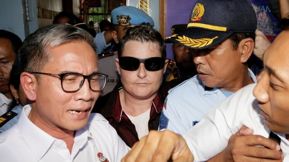 Australian Renae Lawrence (C) surrounded by police leave prison in Bali