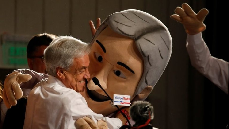Chilean presidential candidate Sebastian Pinera (L) embraces a man wearing a mask depicting him during a gathering with supporters after leading in the first round of general elections in Santiago, Chile November 19, 2017