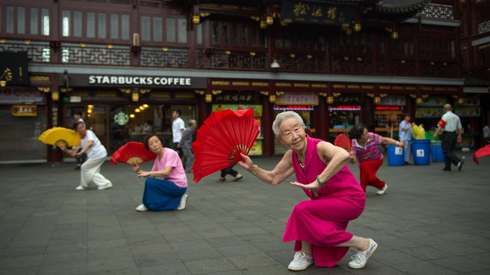 Women do morning exercises in front of a Starbucks restaurant on July 24, 2014 in Shanghai