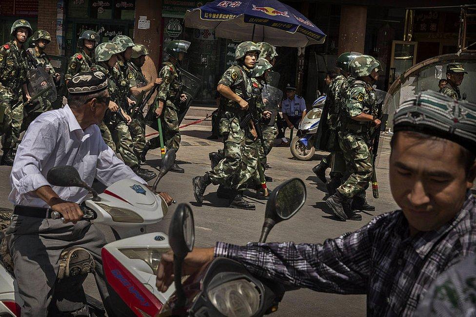 在新疆喀什舉行清晨禱告後,伊瑪目朱姆威·塔希爾(Imam Jumwe Tahir)被襲擊者殺害。圖為身穿防暴服的中國武警在艾提尕爾清真寺外警戒(2014年7月30日資料照片)。