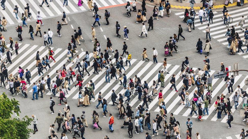 Un cruce de calle repleta de personas.