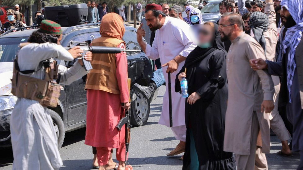 Un talibán apunta a uno de los manifestantes.