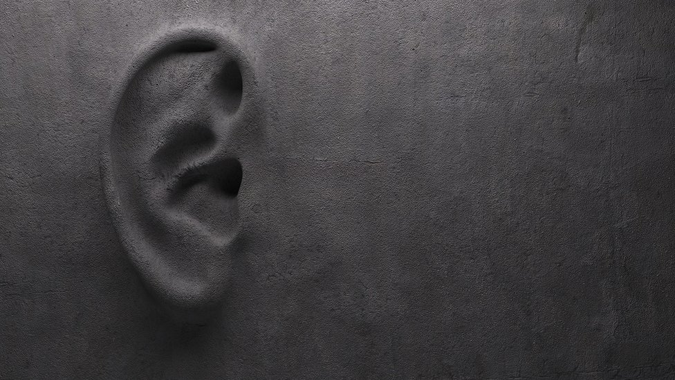 """A grey concrete wall, with an ear sculpted in it - """"ear on wall"""" concept."""