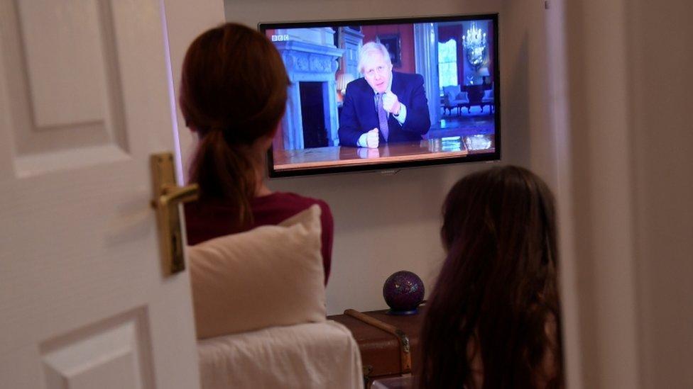 Dos mujeres de espaldas miran el mensaje televisivo de este domingo de Johnson.
