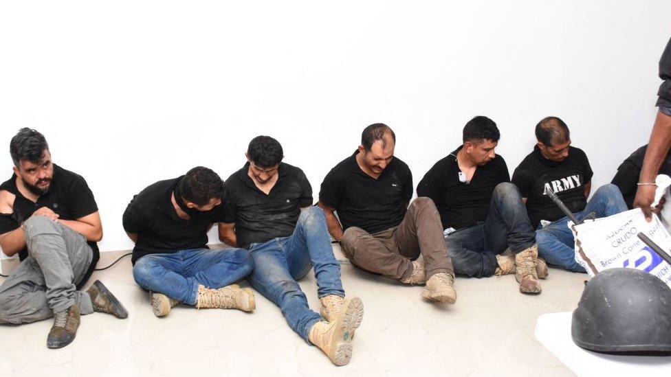 Colombianos arrestados ante la policía haitiana.