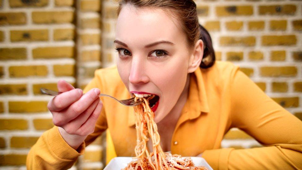 Mujer joven comiendo un plato de pasta en primer plano.