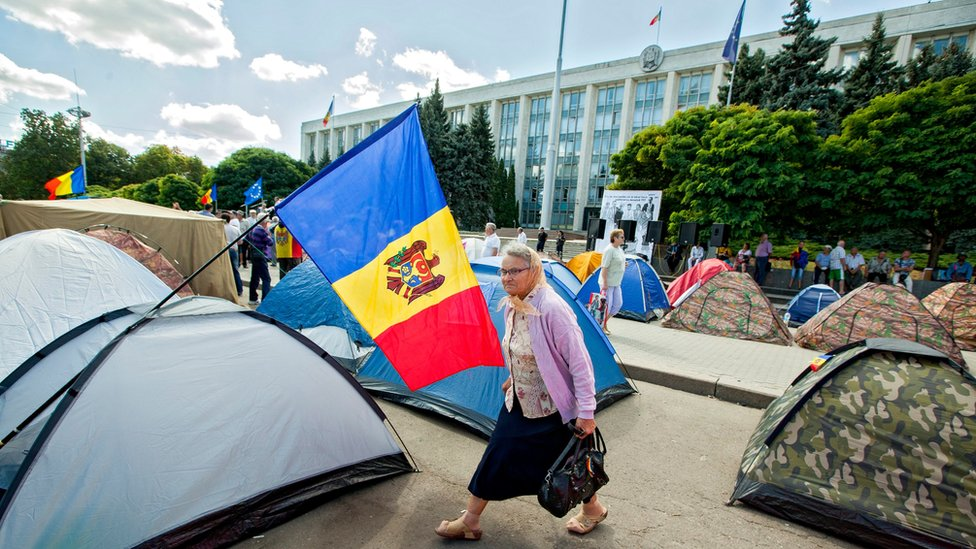An elderly woman passes tents in front of a government building in Moldova