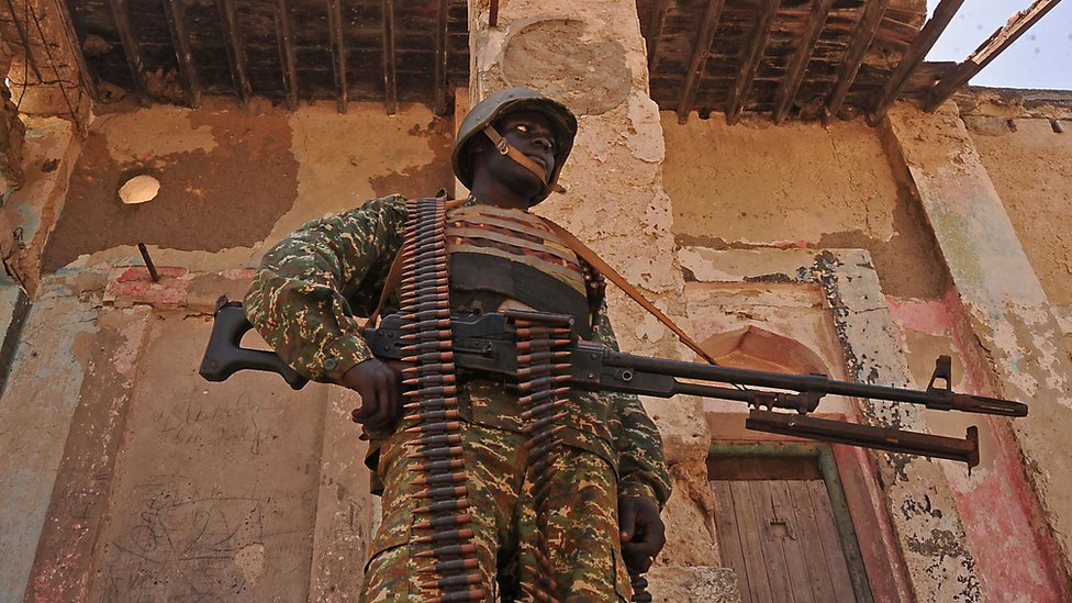 "A Ugandan soldier patrols a back street in the southern town of Merka, 90km north of Somalia""s capital Mogadishu, on 17 July 2016."