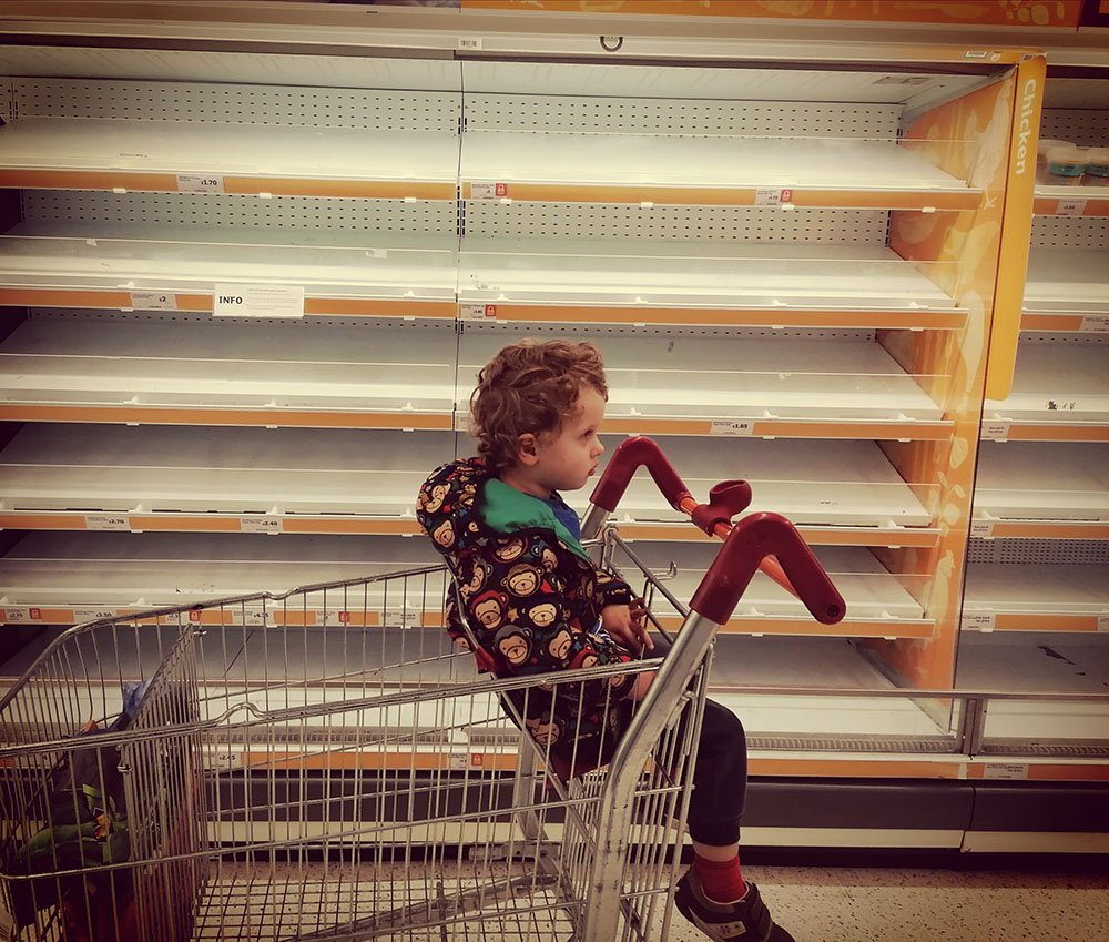 Child next to empty shelves in supermarket
