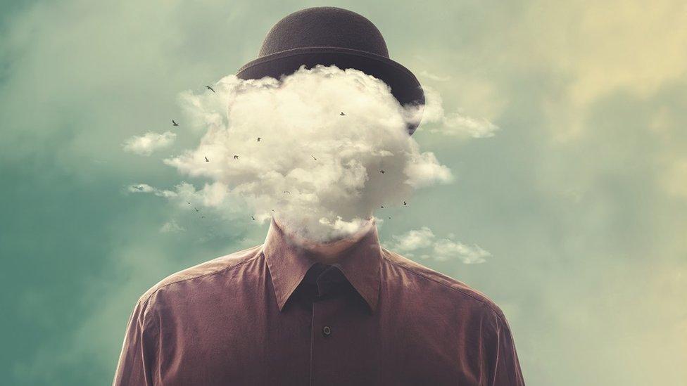 Montaje surrealista: un hombre con un sombrero caído y una nube en su cara.