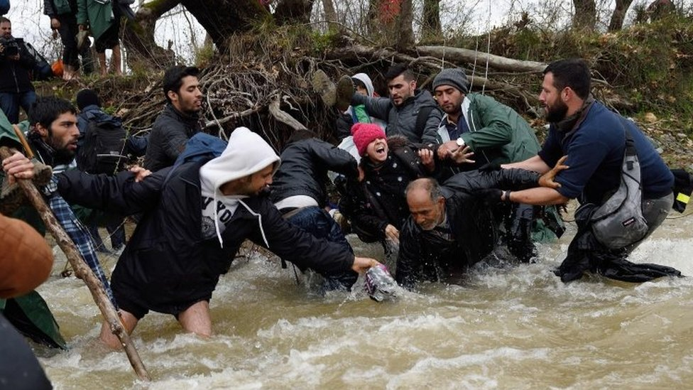 Migrants fall into a river on their way to Macedonia. Photo: 14 March 2016