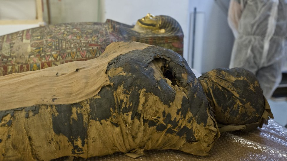 The mummy is seen lying down in place by casing