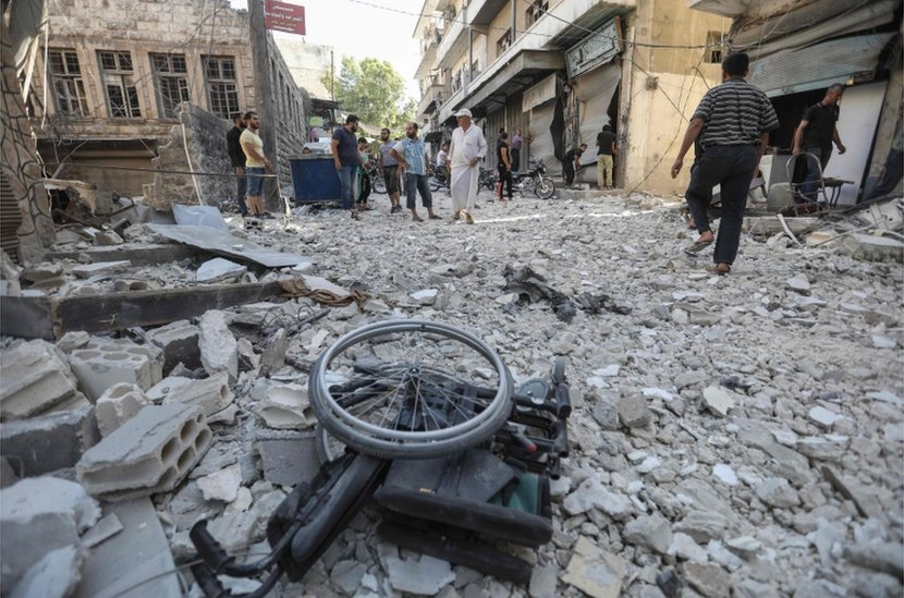 A wheelchair in the rubble of destroyed buildings in Ariha on Wednesday