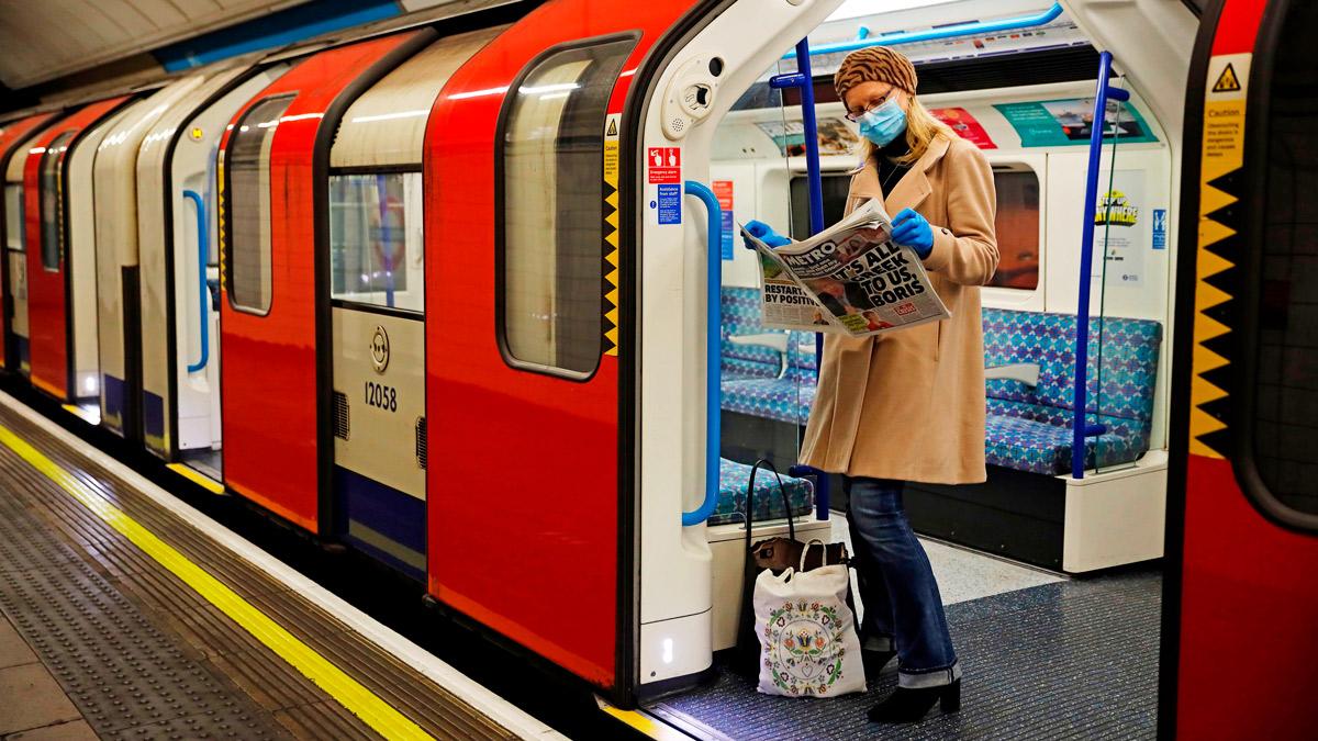 Женщина в маске читает газету в поезде лондонского метро, 11 мая 2020 г.