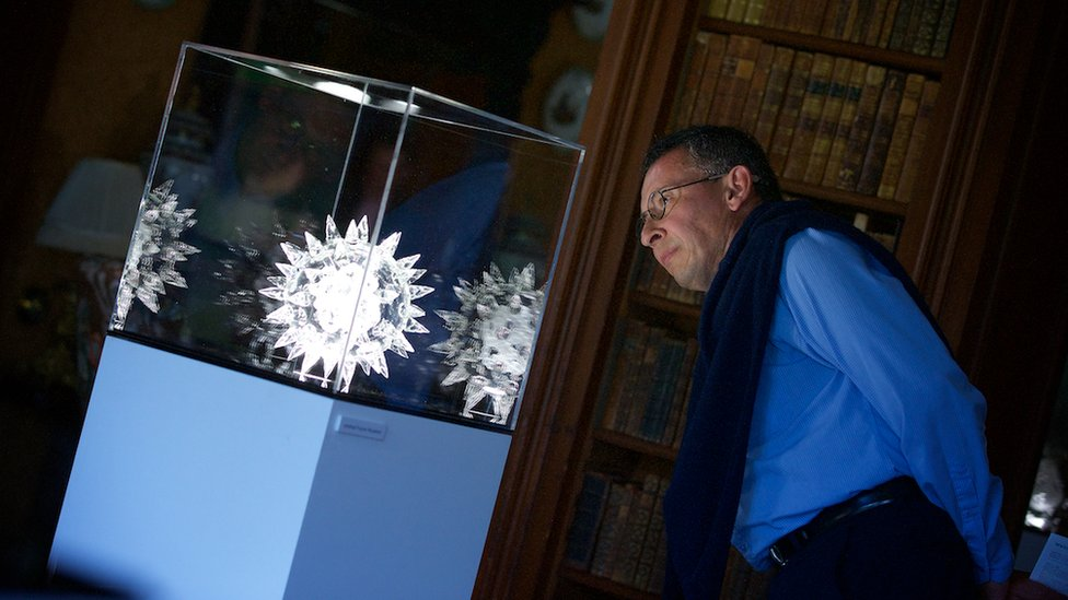 Man looking at Luke Jerram artwork