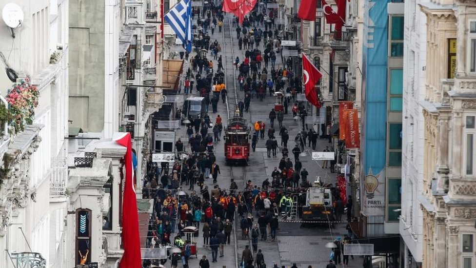 People walk on Istiklal Street near the site of Saturday's bomb explosion in Istanbul (20 March 2016)