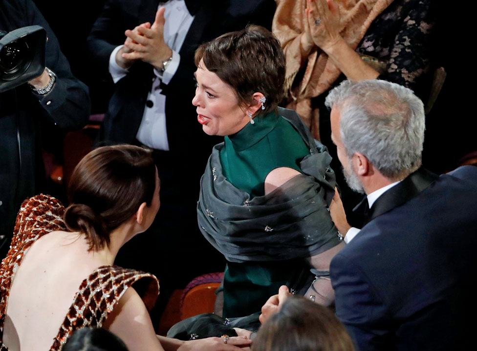 Olivia Colman stands to accept the Best Actress award