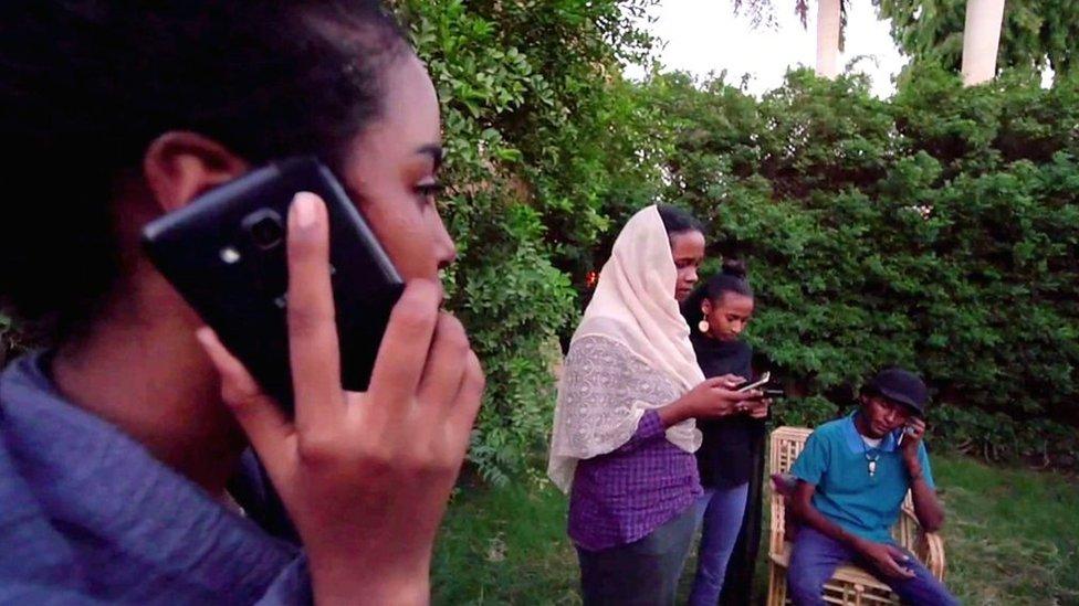 Manifestantes con celulares en Sudán