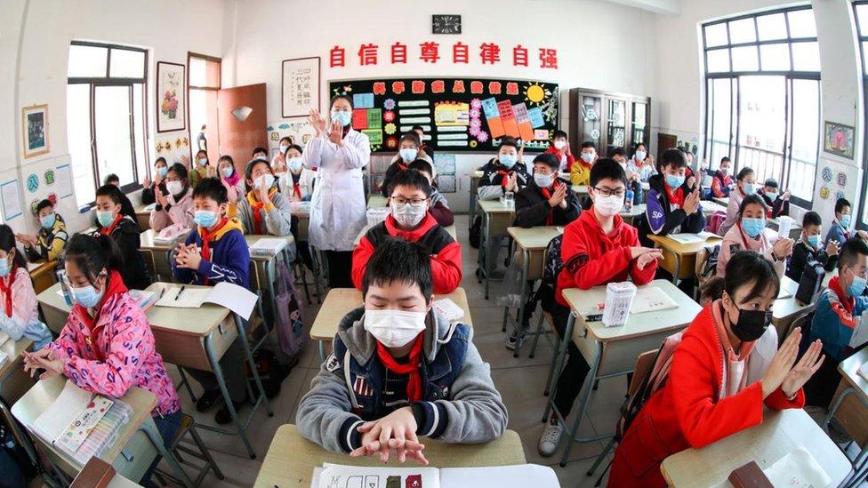 Alumnos asiáticos con tapabocas y limpiándose las manos.