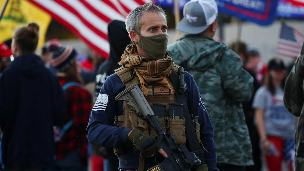 """A supporter of US President Donald Trump carries a semi-automatic riflevduring a """"Stop the Steal"""" protest in Phoenix, Arizona, on 8 Nov 2020"""