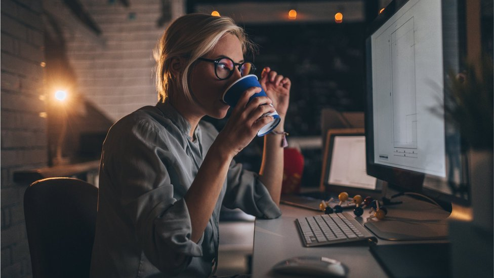 A woman drinking coffee from a paper cup and looking at a computer screen