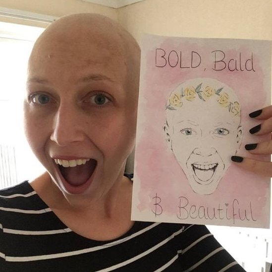 Kirsty Hopgood holding a 'bold, bald and beautiful' card